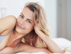 A young beautiful woman lies on the bed with her head in her hand and smiles at the camera