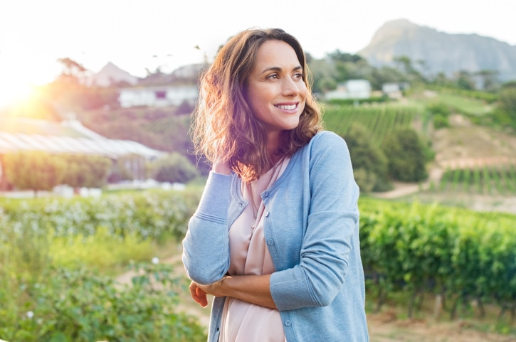 A woman standing in a field of wine grapes.